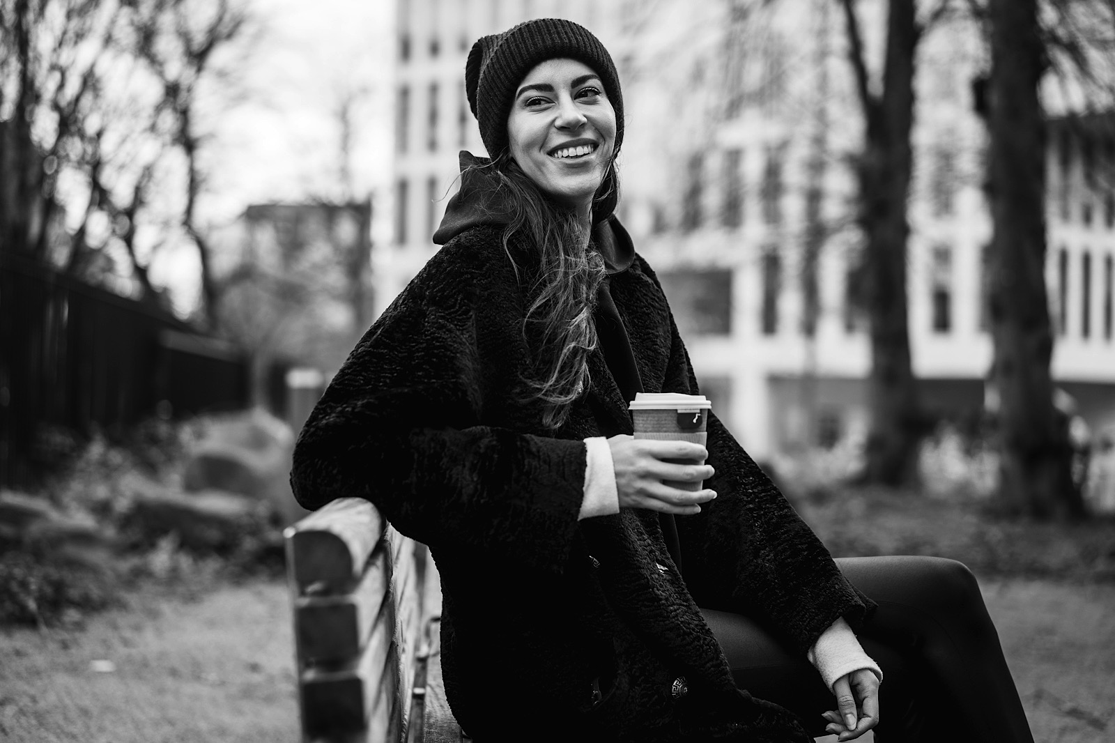 woman sat on bench holding coffee during creative linked in corprate headshot shoot