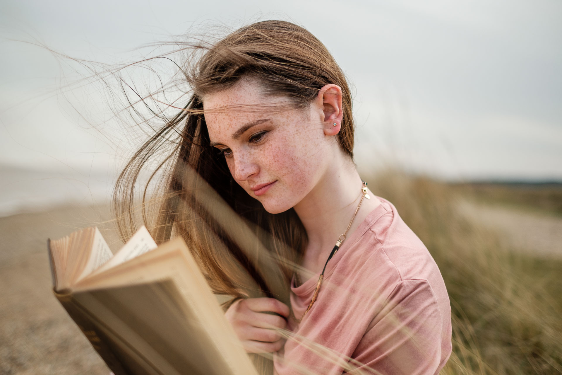 Girl reading book on the beach in Suffolk