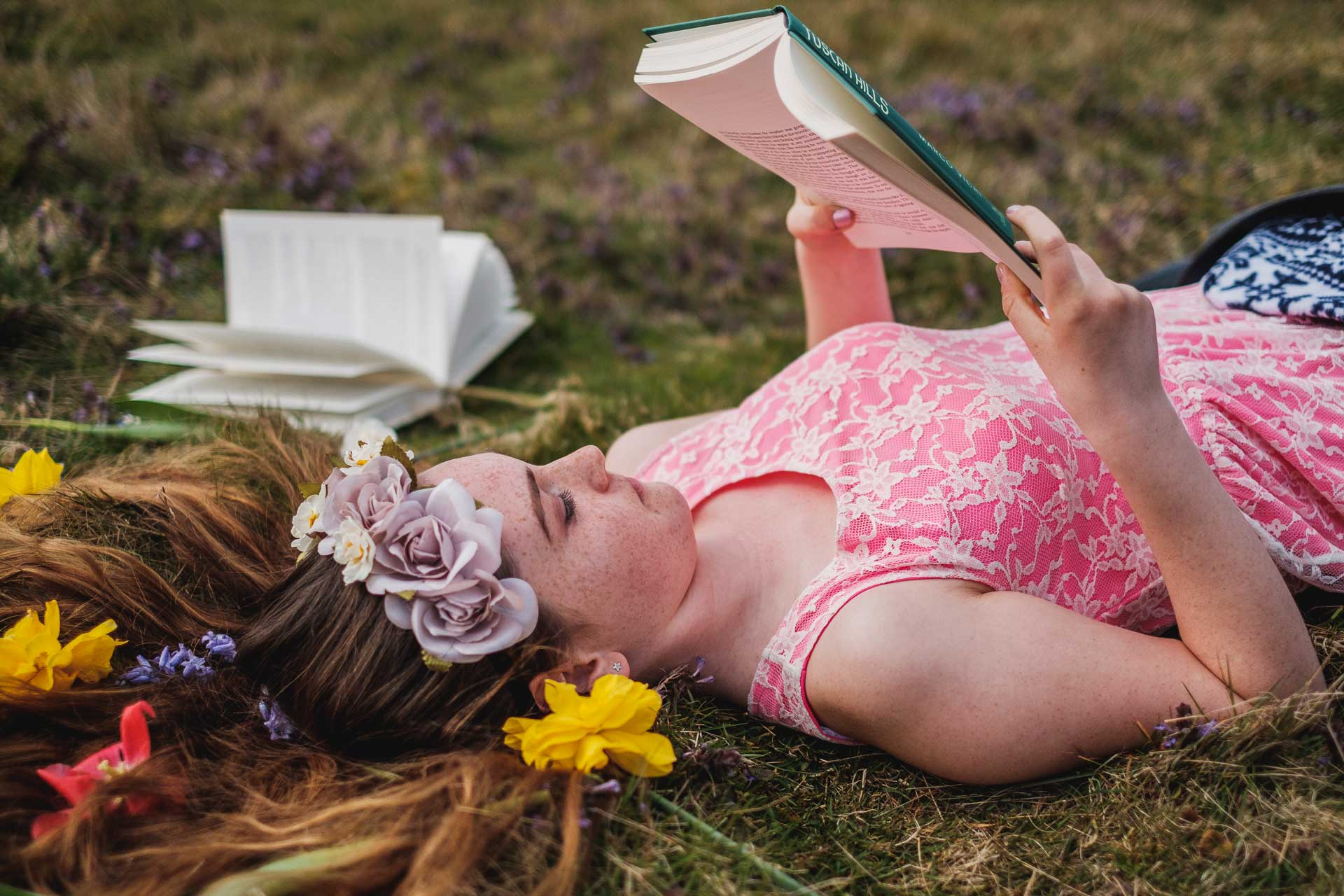 Girl lying on grass reading book
