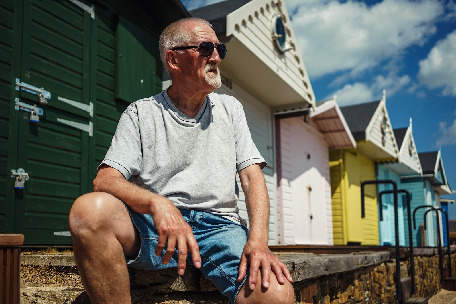 Portrait of a elderly man sitting by a row of beach huts in Essex