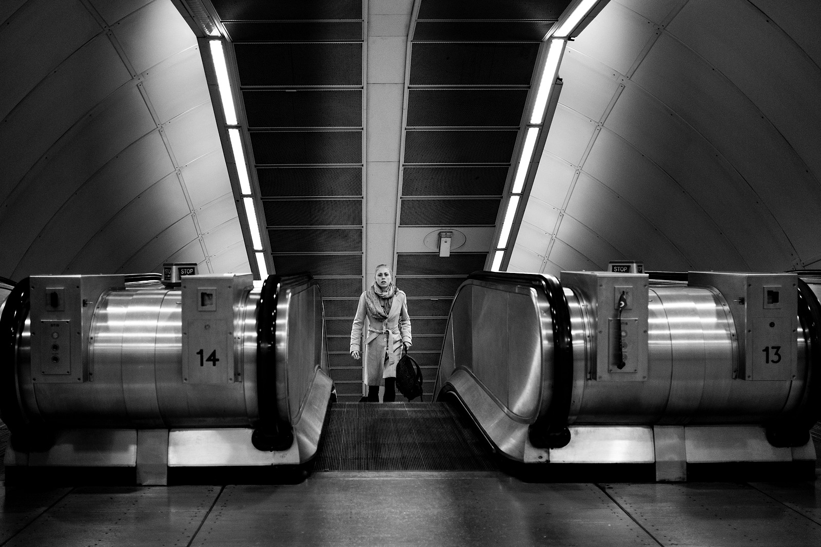 Black and White photo of a girl walking up escalators on the London underground