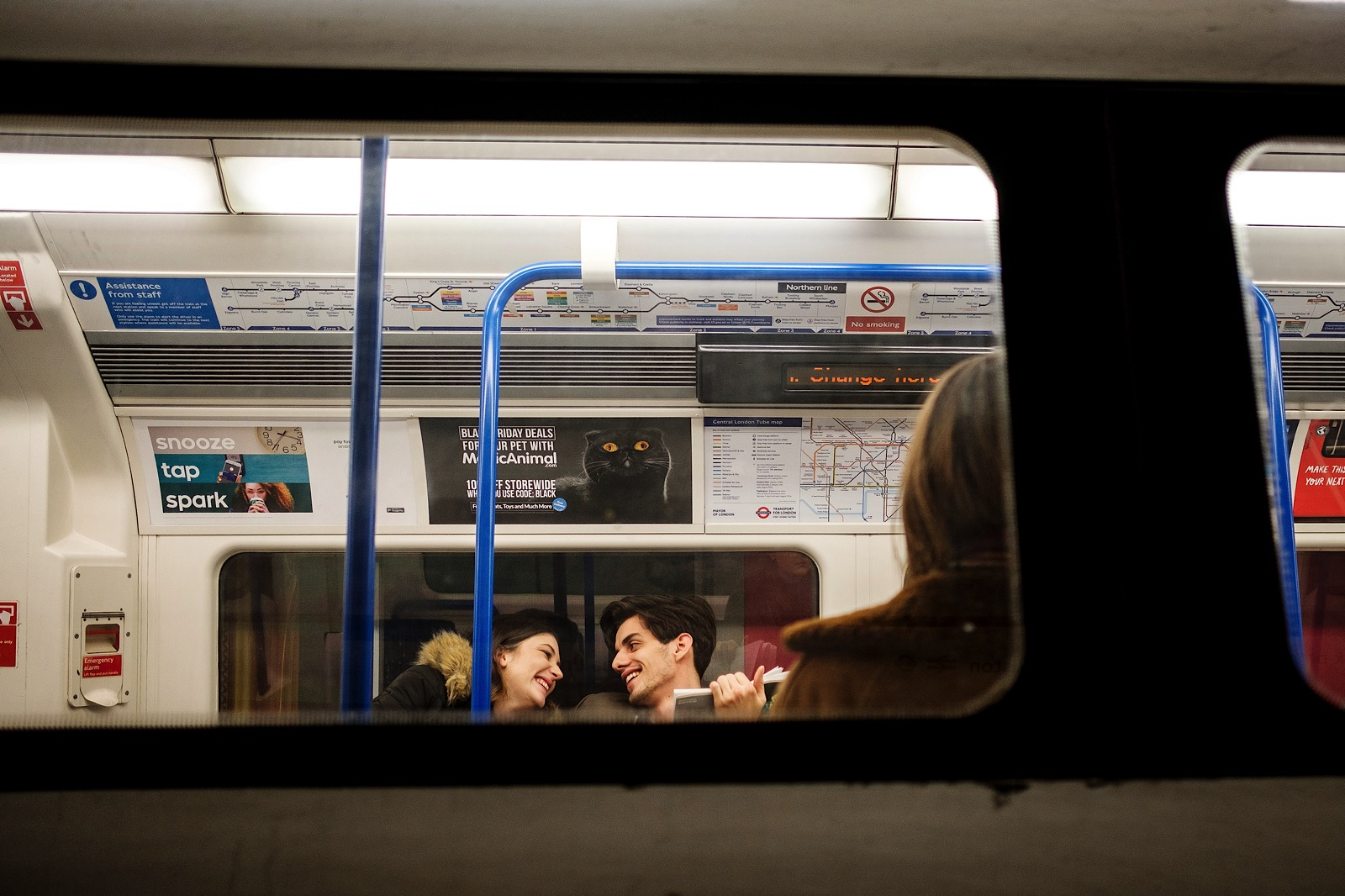 Two people laughing and looking at each other on the London Underground.