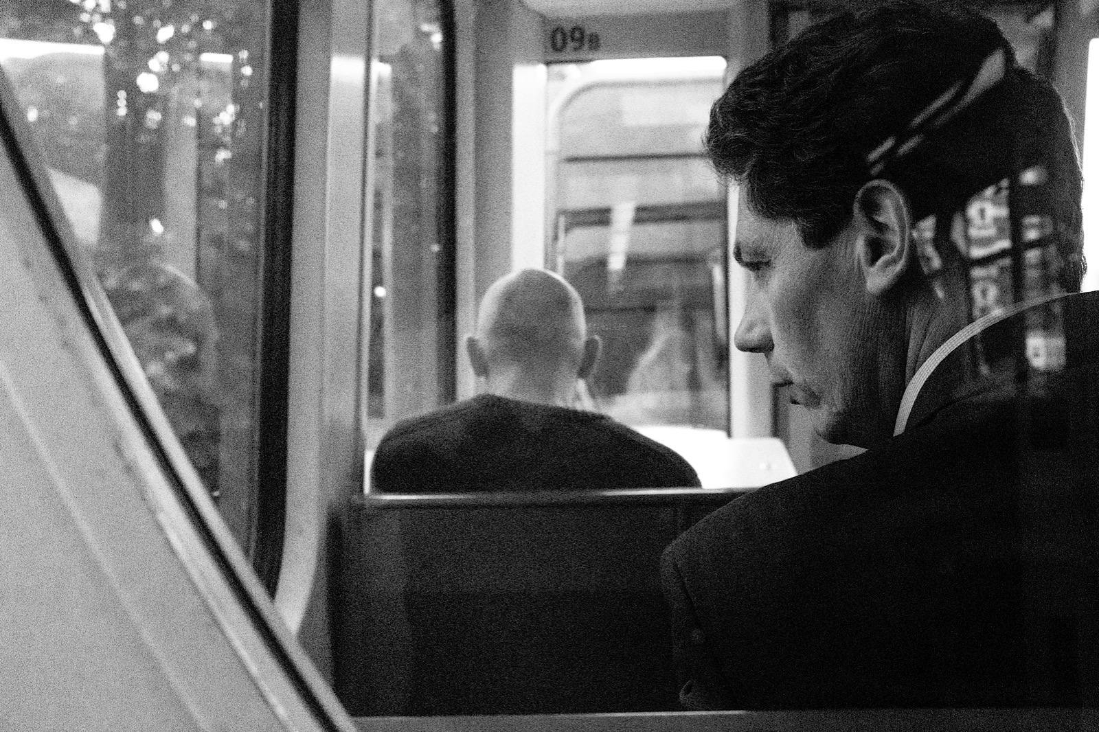 Film Noir style candid portrait of a man sitting on the DLR.