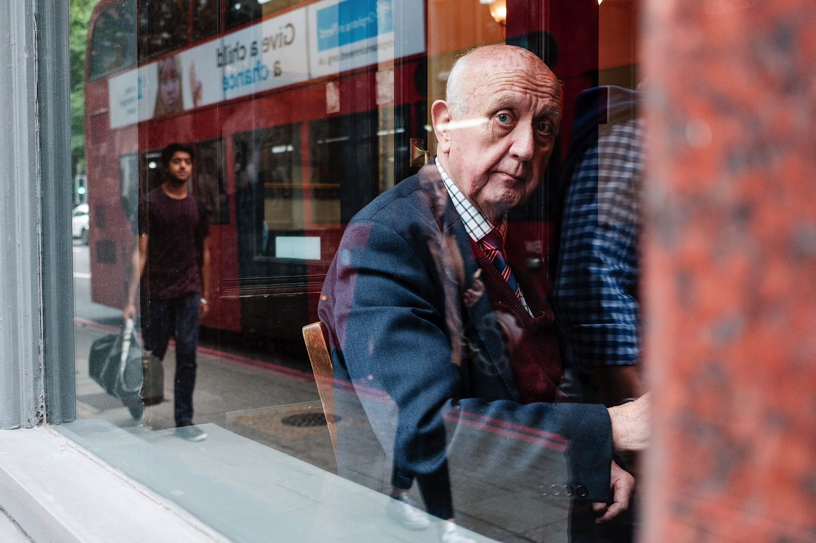 Creative Street Photography of an old man looking through the window, with reflections creating an interesting scene.