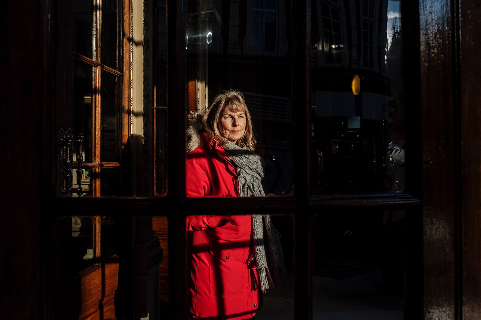 Candid Portrait of a Lady wearing a bright red jacket looking out of the window in London