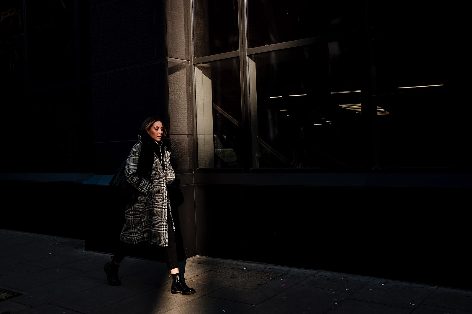 Street Photo of a girl walking into a shaft of light