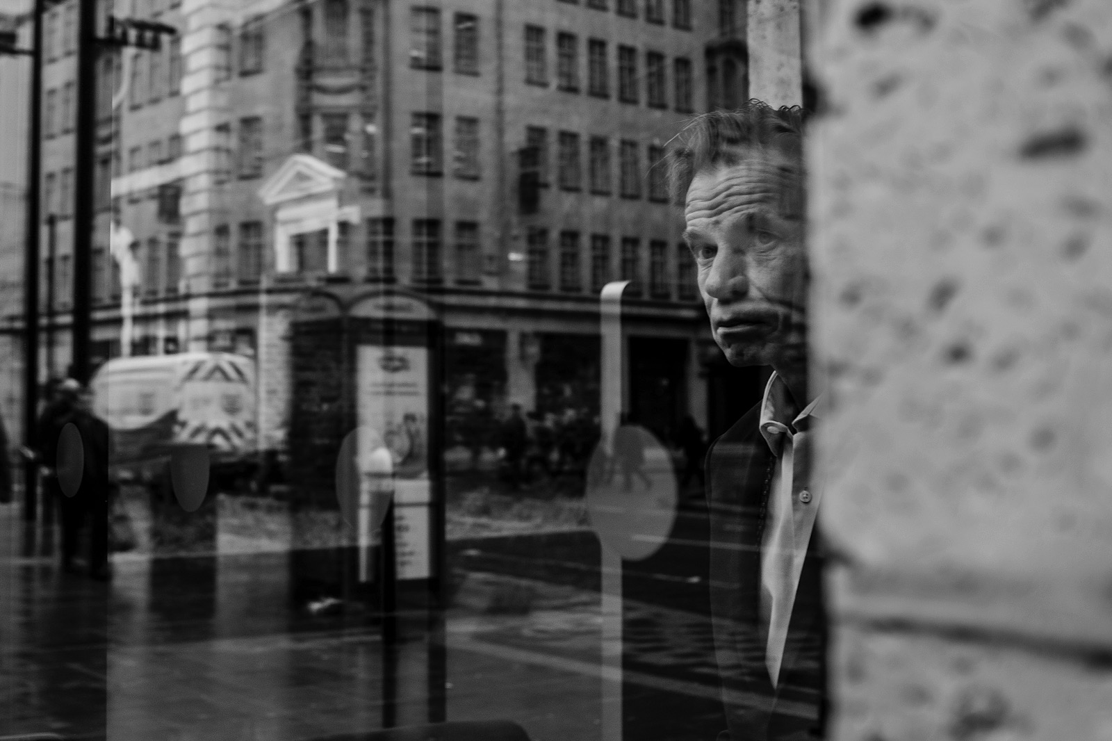 Film Noir Style photo of a man looking through the window with various reflections obscuring him.