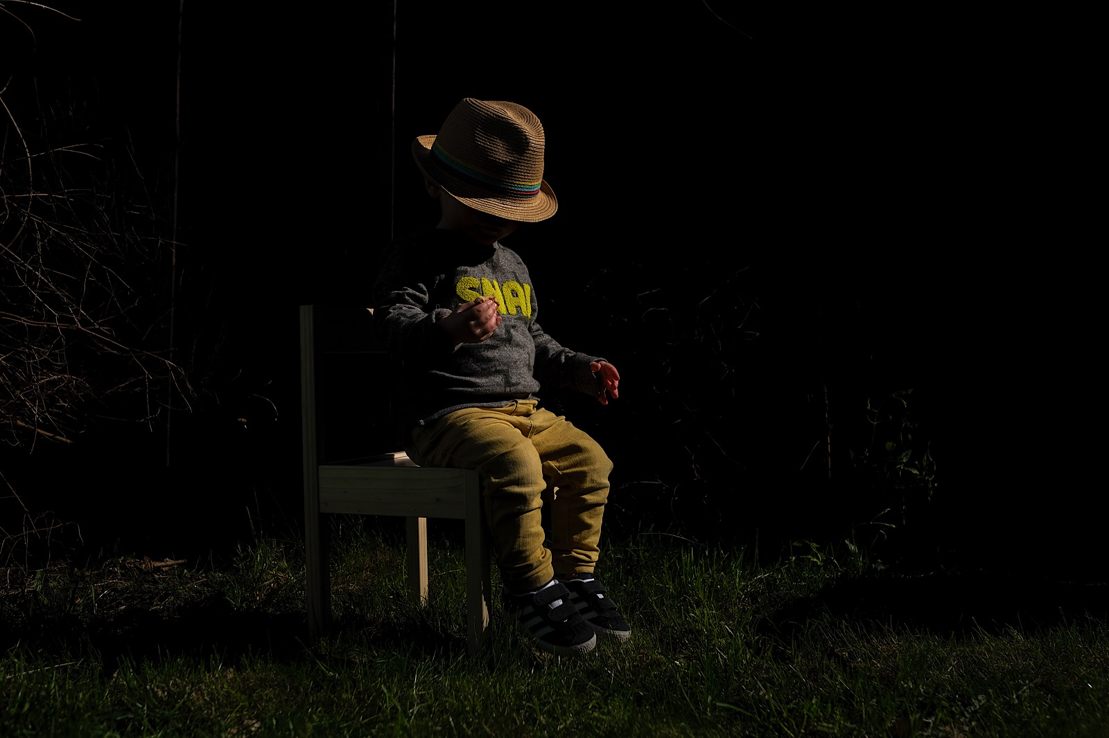 little boy sat in hat on small chair in garden during pandemic