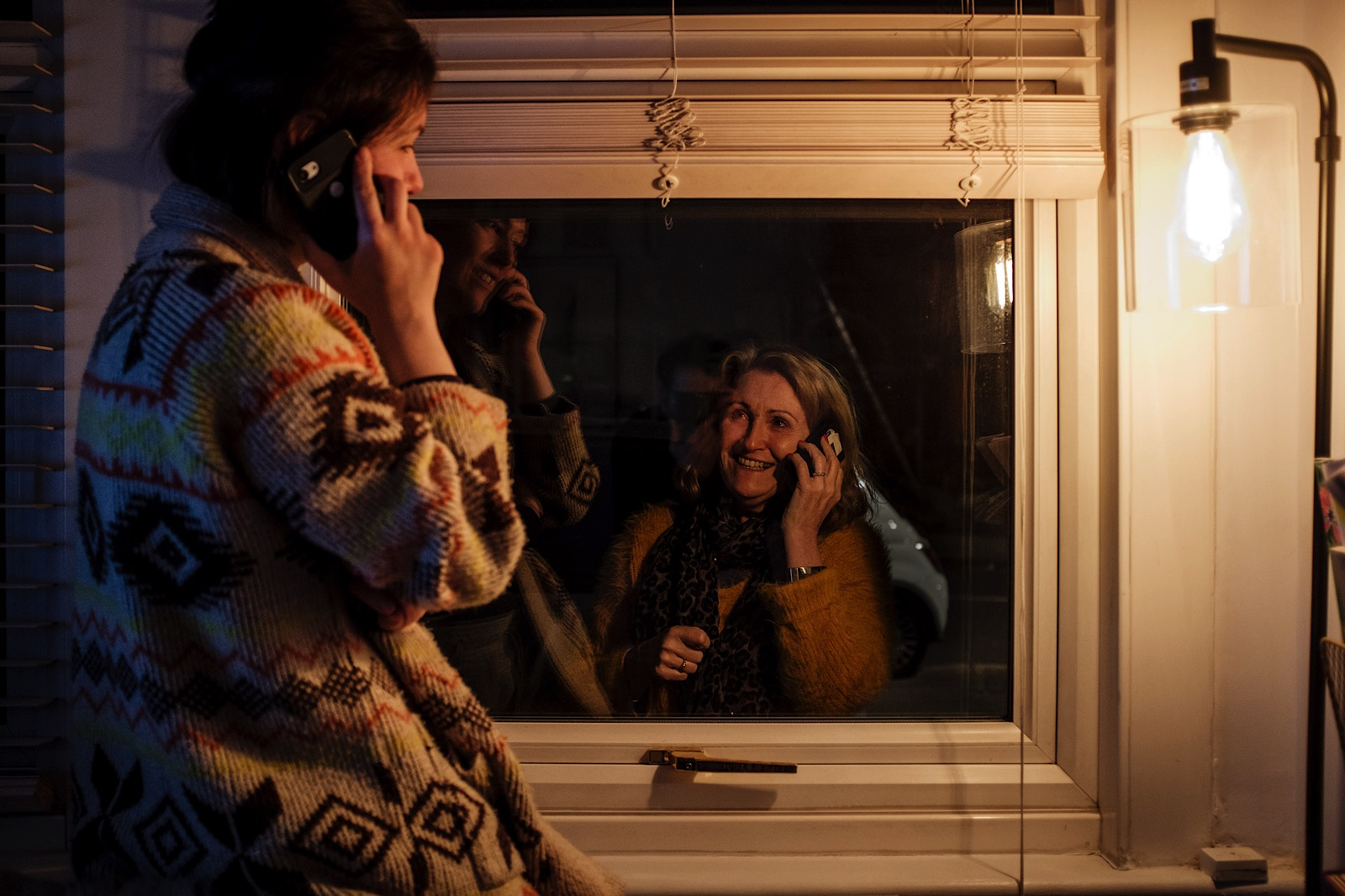mother and daughter talking on mobiles either side of a window during covid-19 pandemic