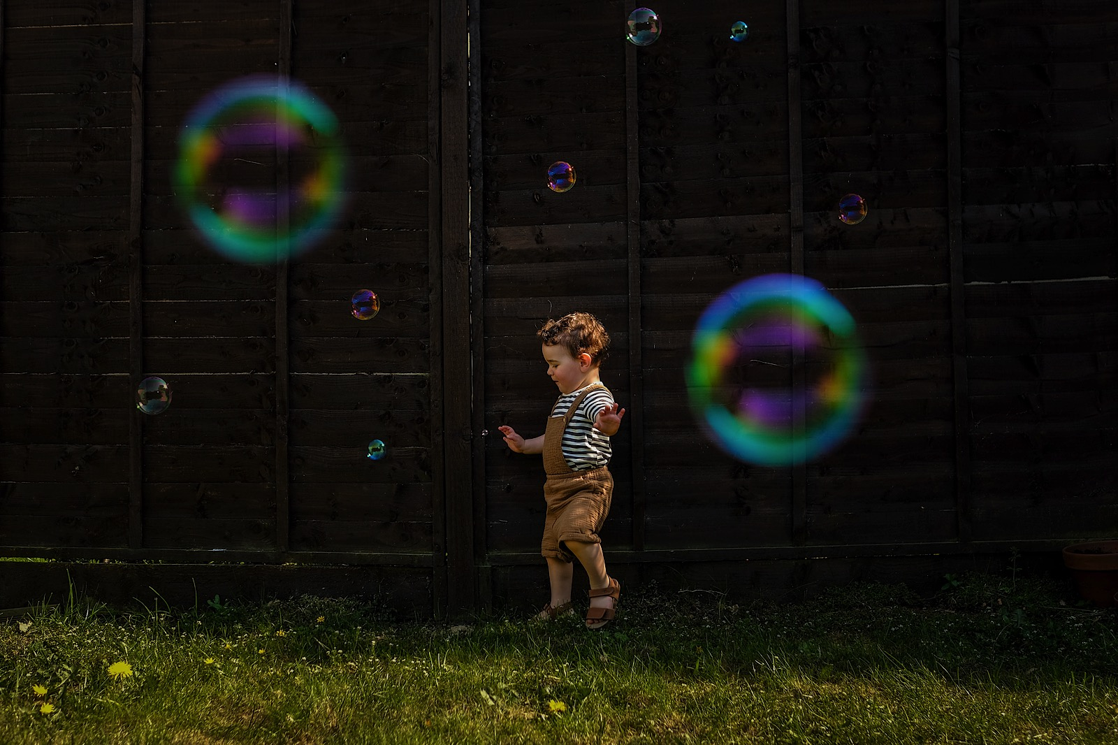 little boy in dungarees running chasing bubbles in garden during covid-19 pandemic