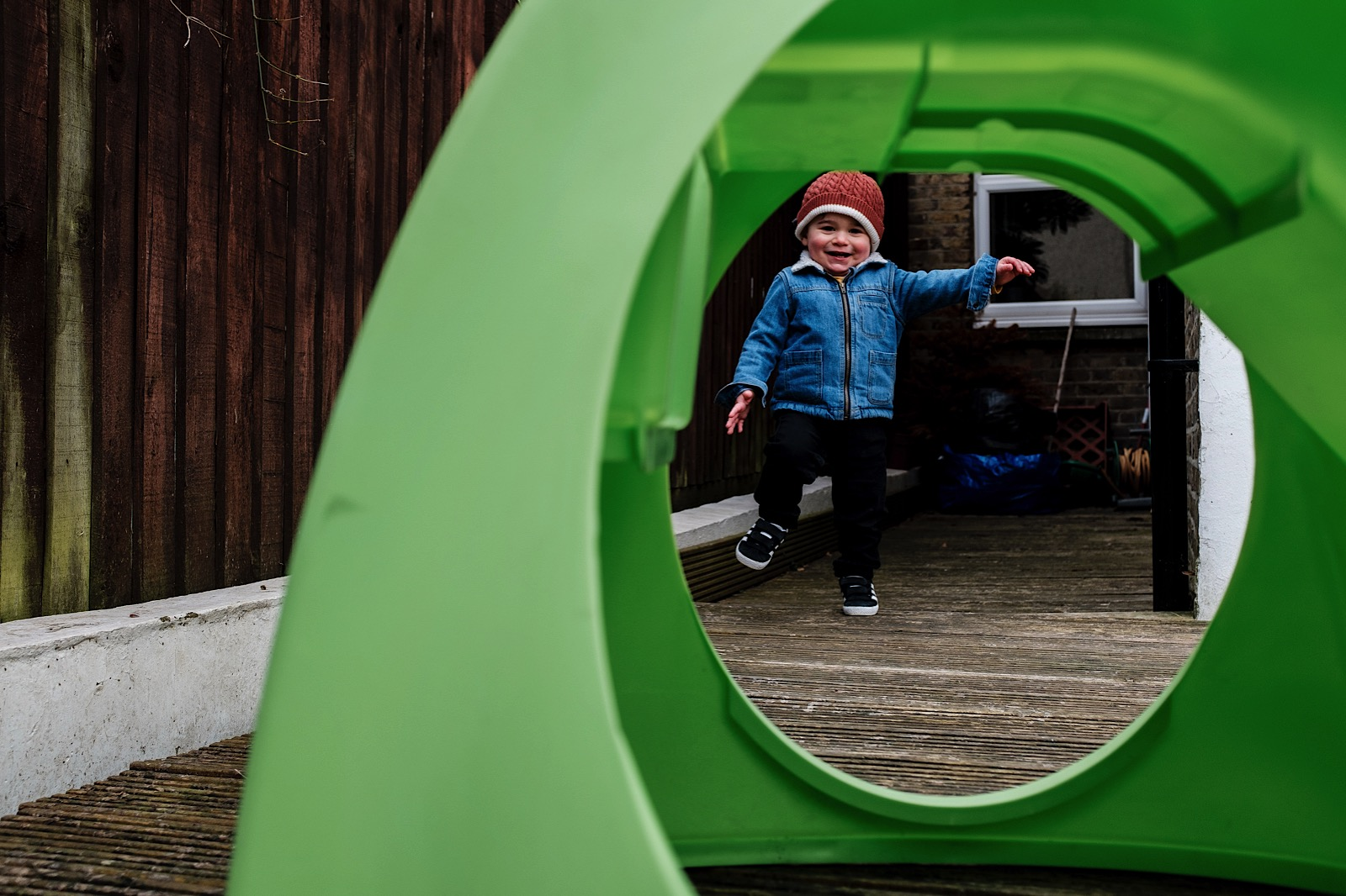 Image of little boy wearing denim jacket and red bobble hat caught through green slide opening