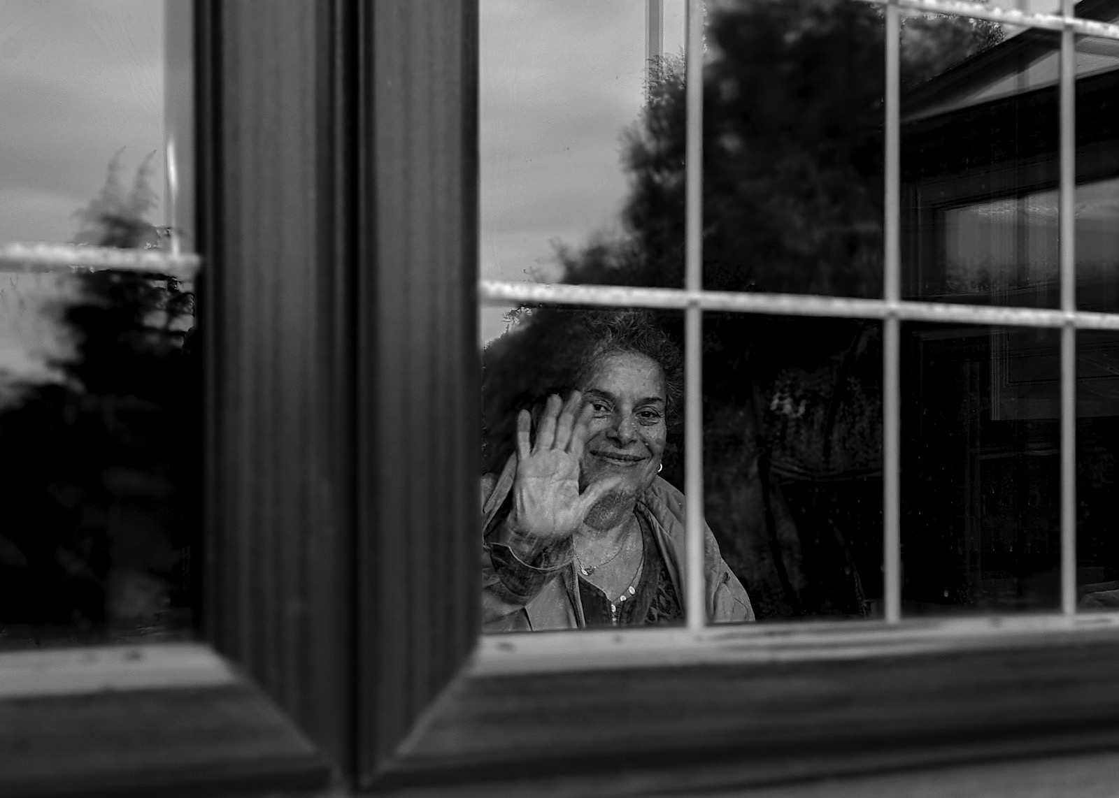 Image of woman smiling placing her hand against glass window during Covid-19 pandemic