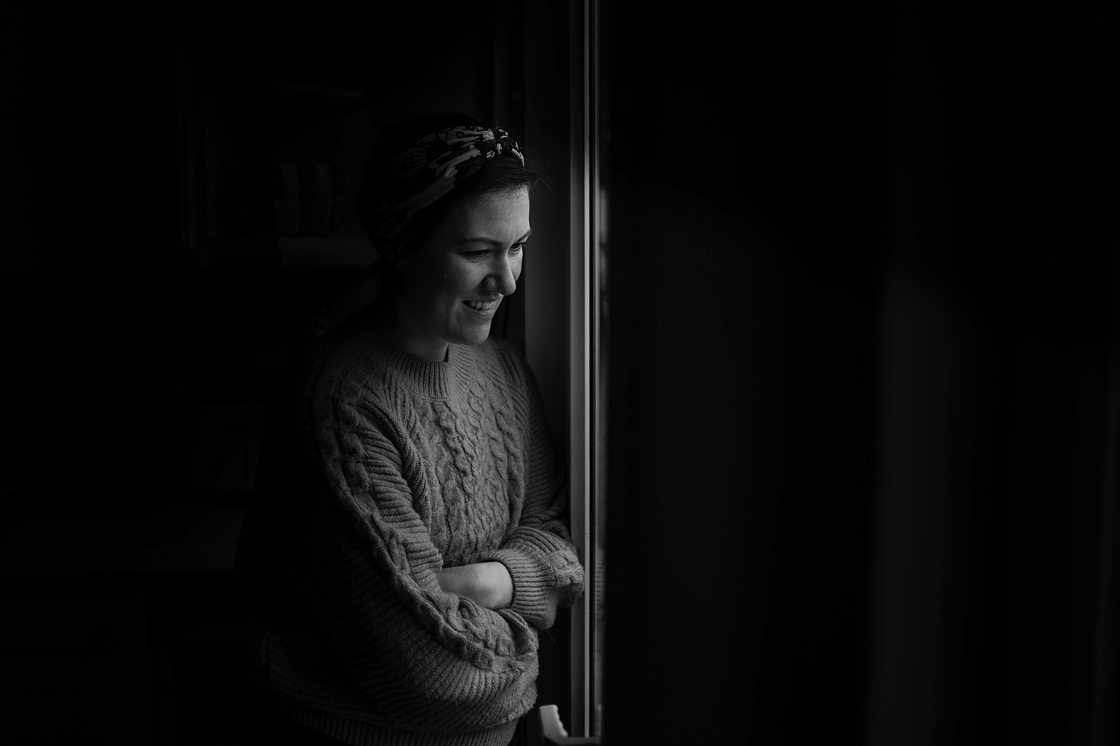 Documentary portrait of woman looking out of a window