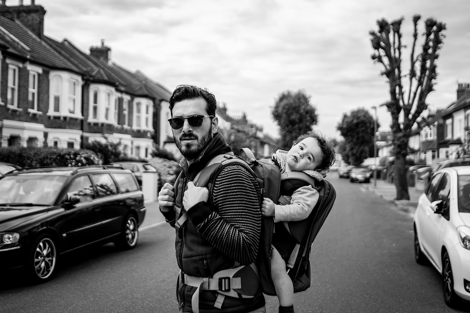 London Documentary photographer Tarik Ahmet in Street with his son on his back