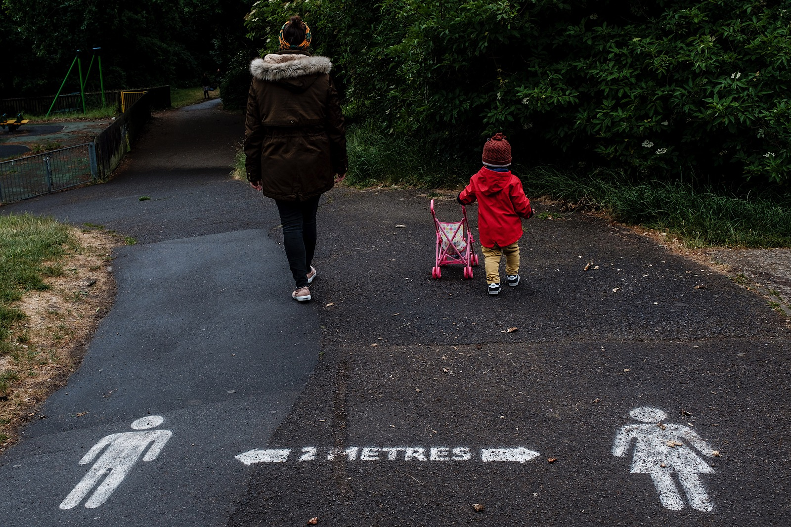 Mother and child walking down path with 2 meter apart sign spray-painted on path in foreground