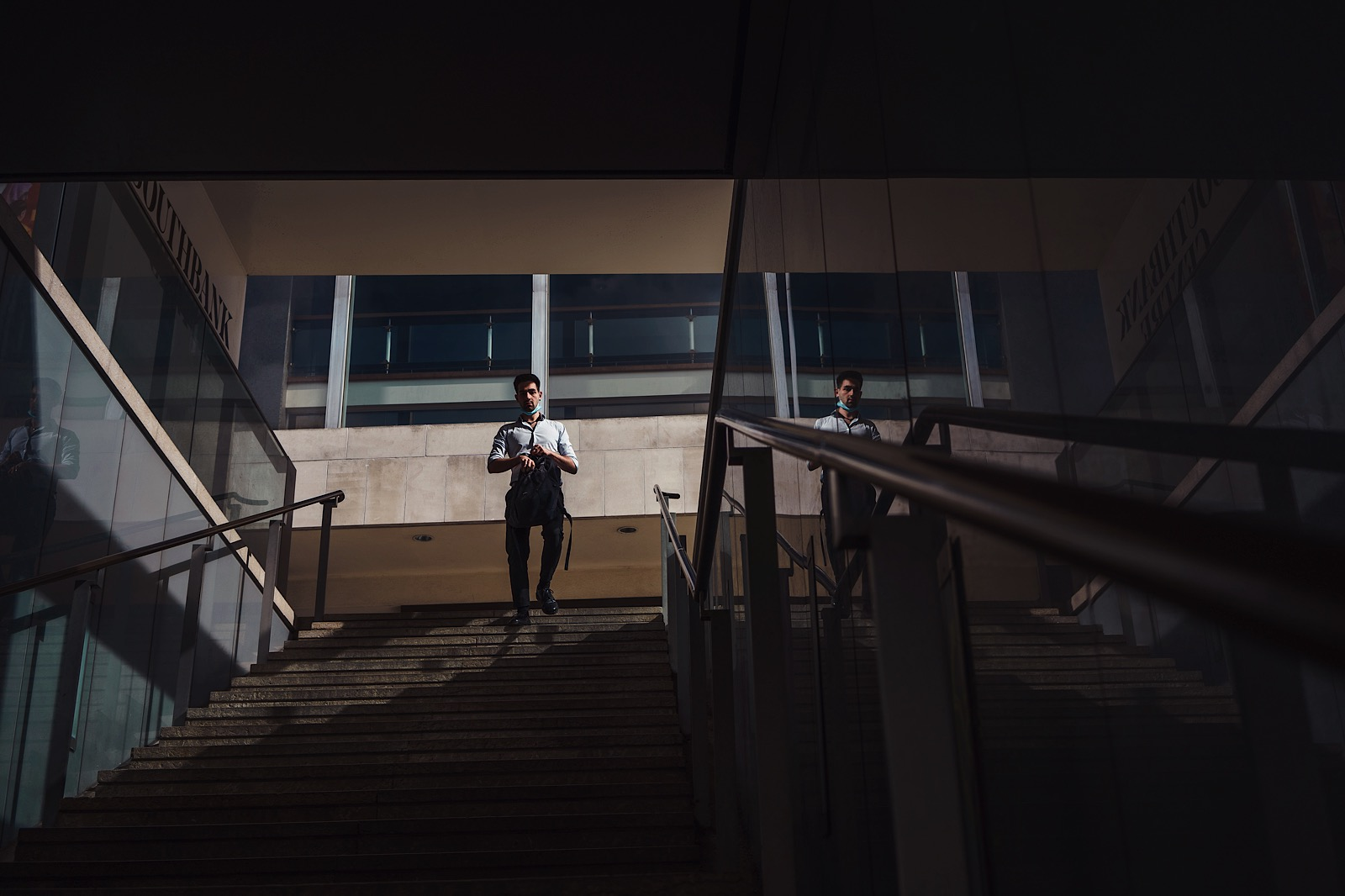 Street photography showing man running down stairs