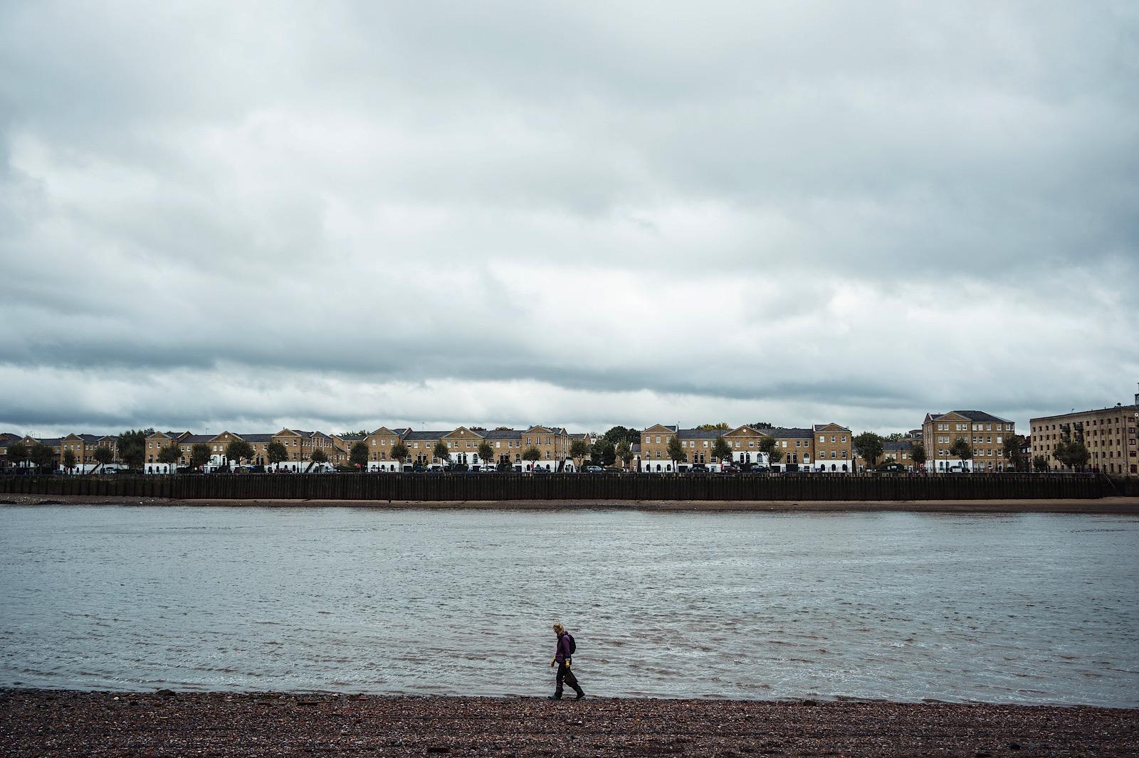 Mudlarker walking along shore of River Thames