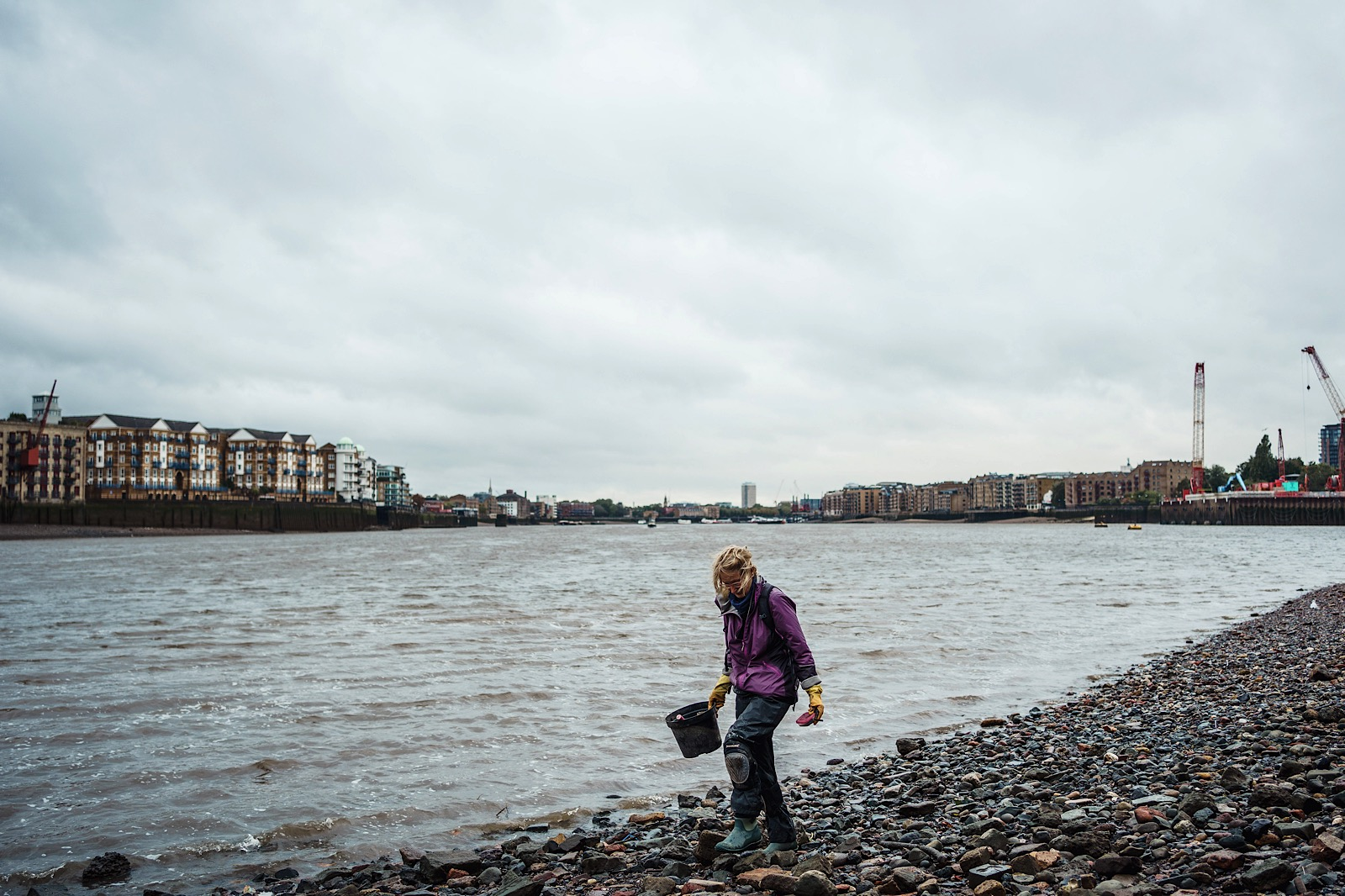 Mudlarker walking with bucket on banks of River Thames in London looking for treasure