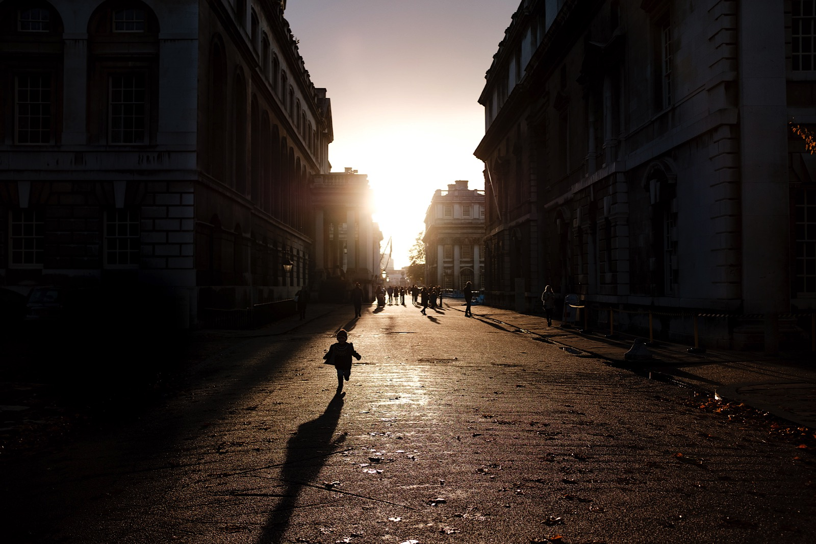 Child running through streets of London during sunset