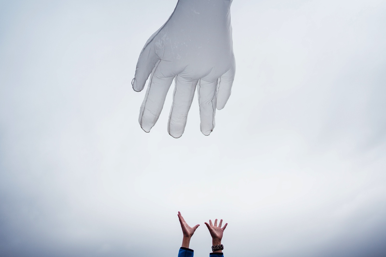 2 hands reaching in air toards big inflatable hand