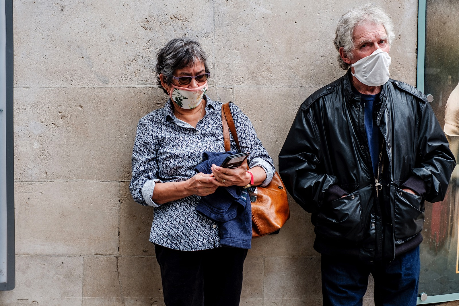 man and woman waiting in line wearing masks
