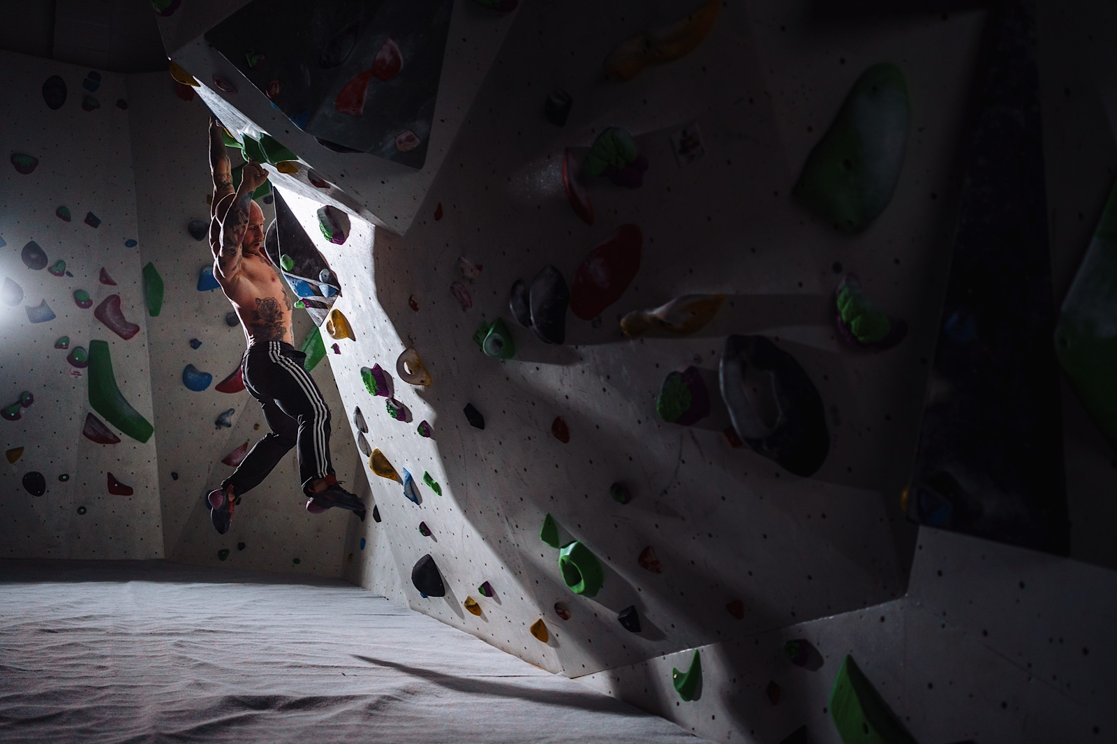 Rockclimber hanging from overhang on climbing wall