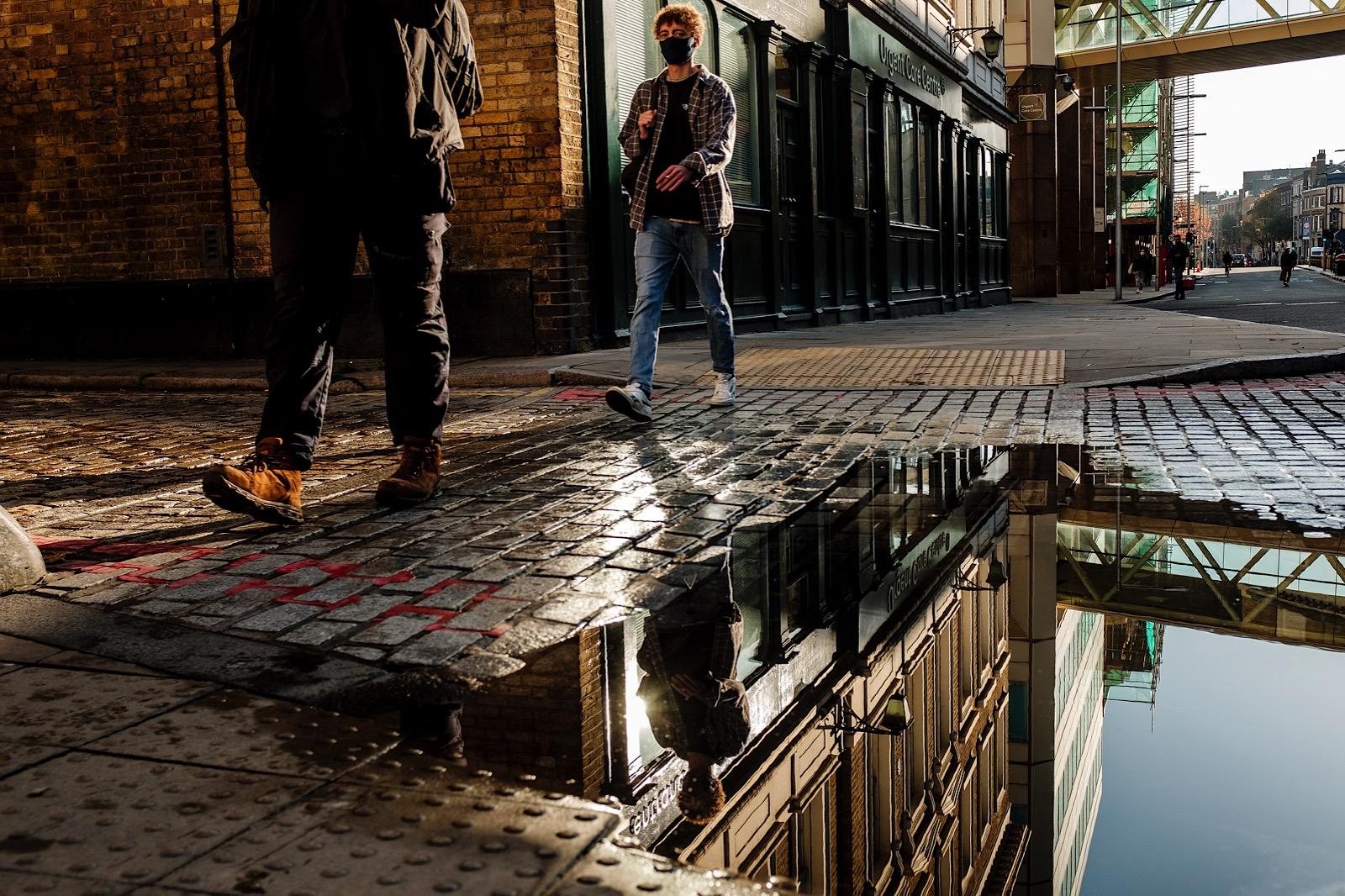 Man walking down London street wearing a mask reflected in the water