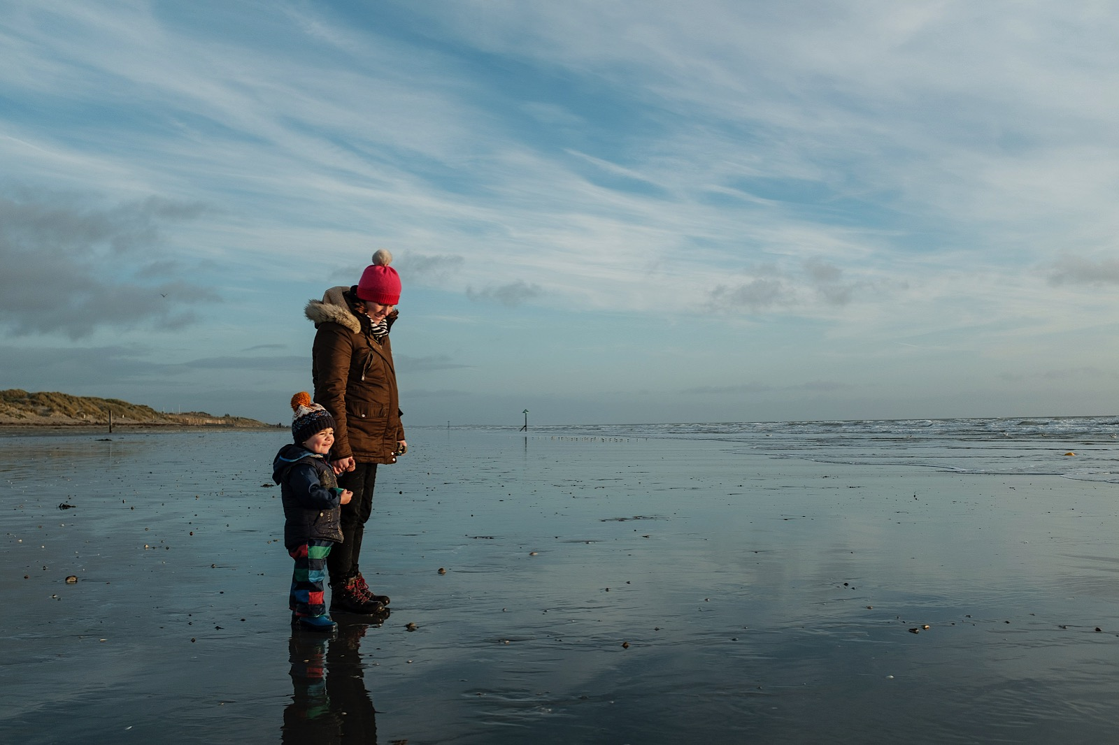 Mother and young child stood on wet beach in winter clothing