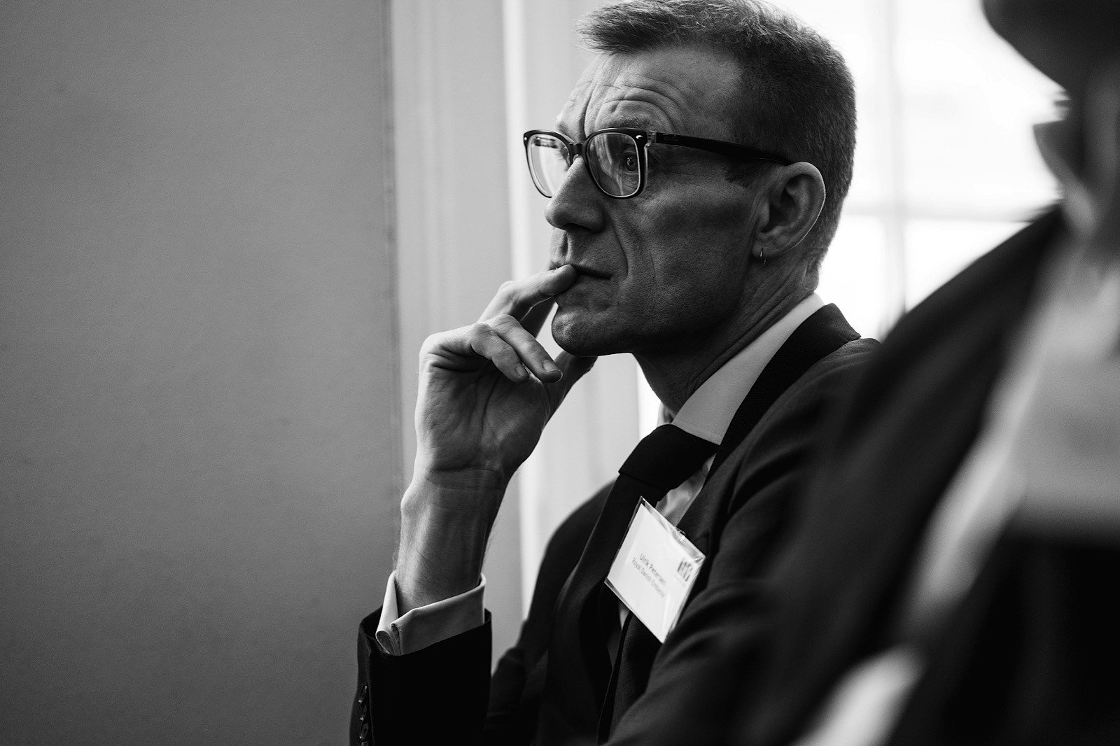 Man with glasses thoughtfully listening to meeting