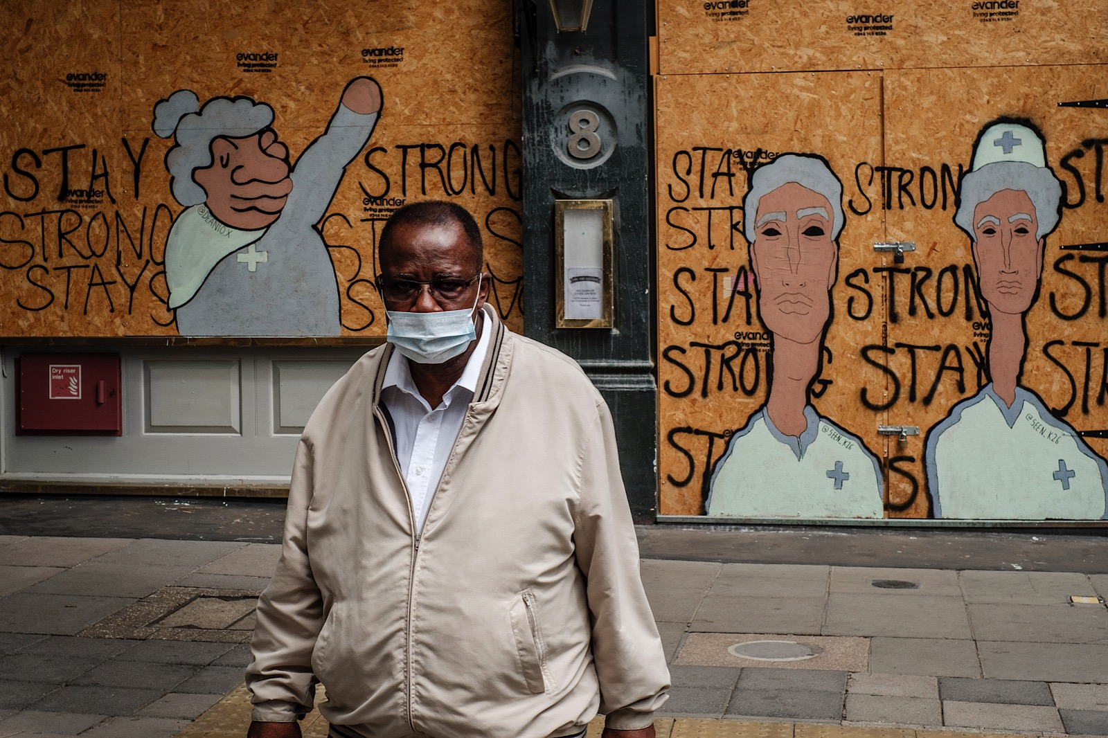 Man wearing a mask during covid in front of street art showing doctors and nurses