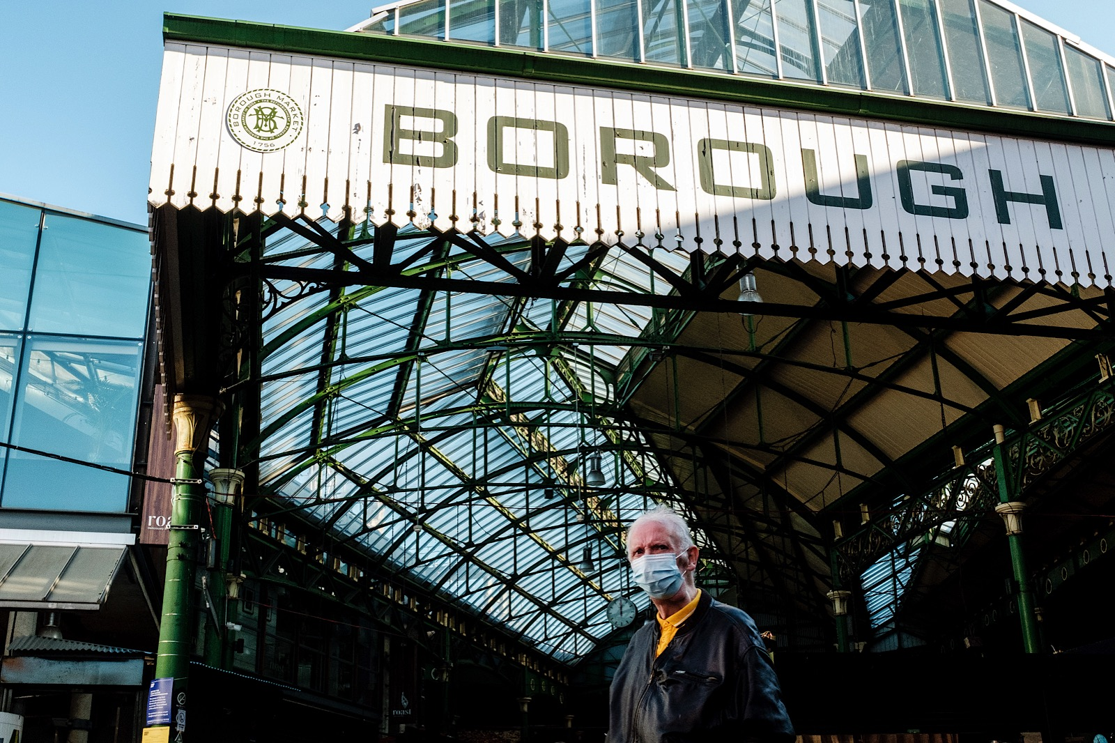 Man wearing a mask under the Borough Market, London sign