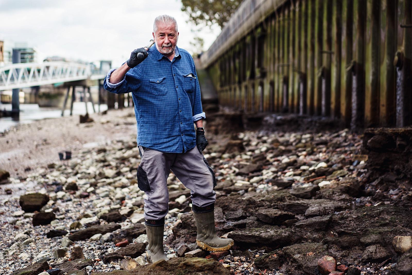 Mudlarket stood on Banks of River Thames with tool over shoulder