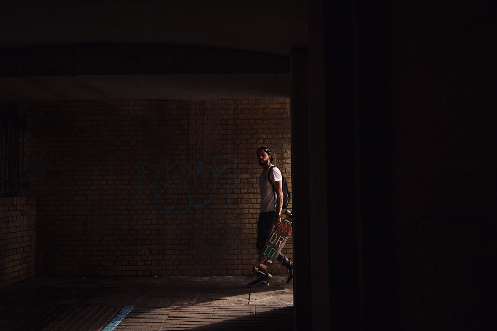 Man walking with skateboard in his hand