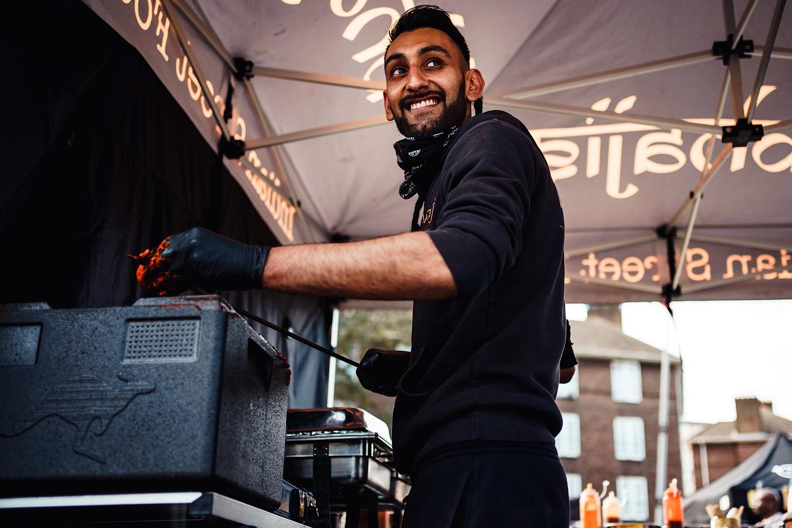man preparing food outside grinning