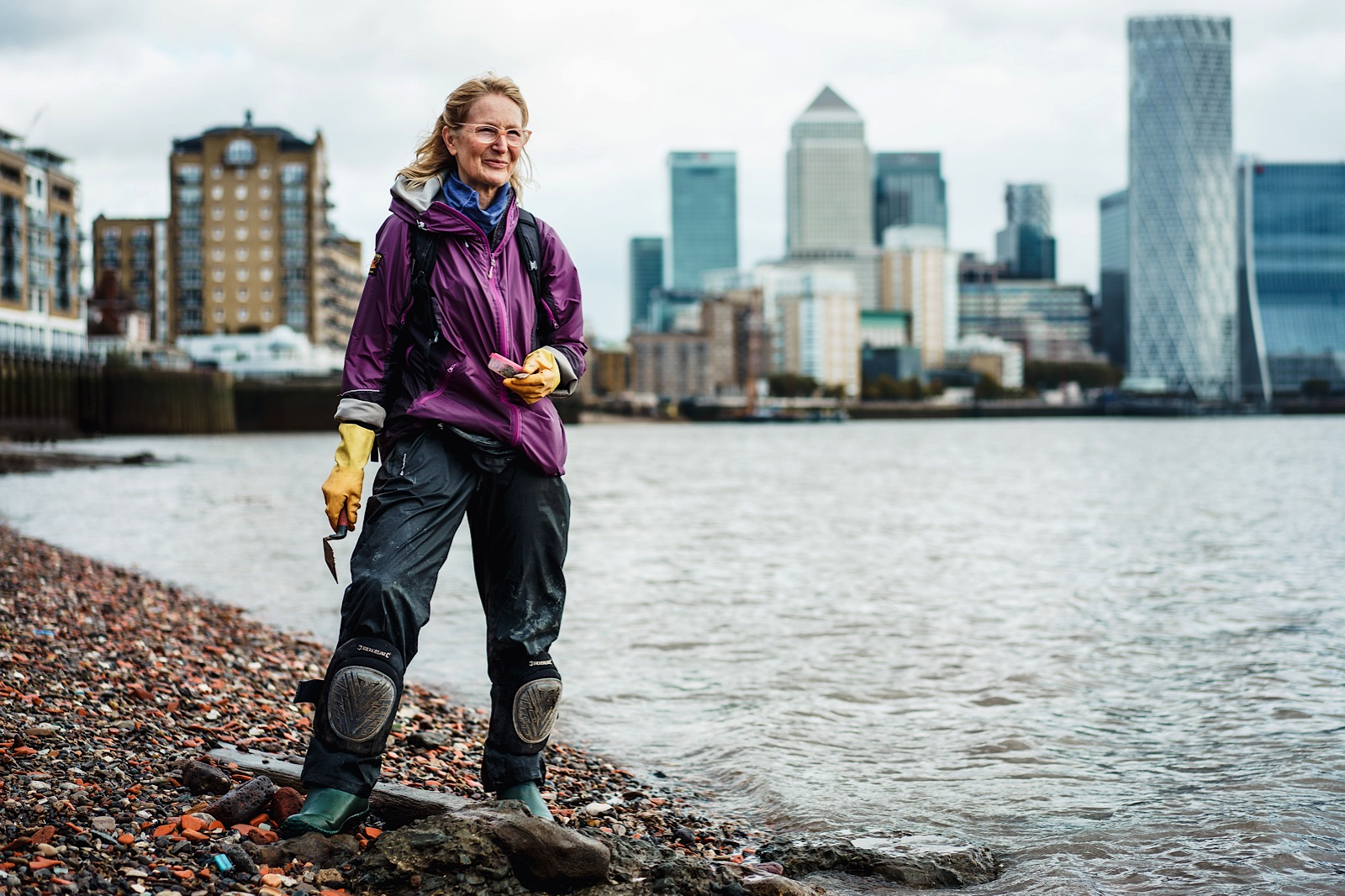 Mudlarker on shore of River Thames with trowel in her hand