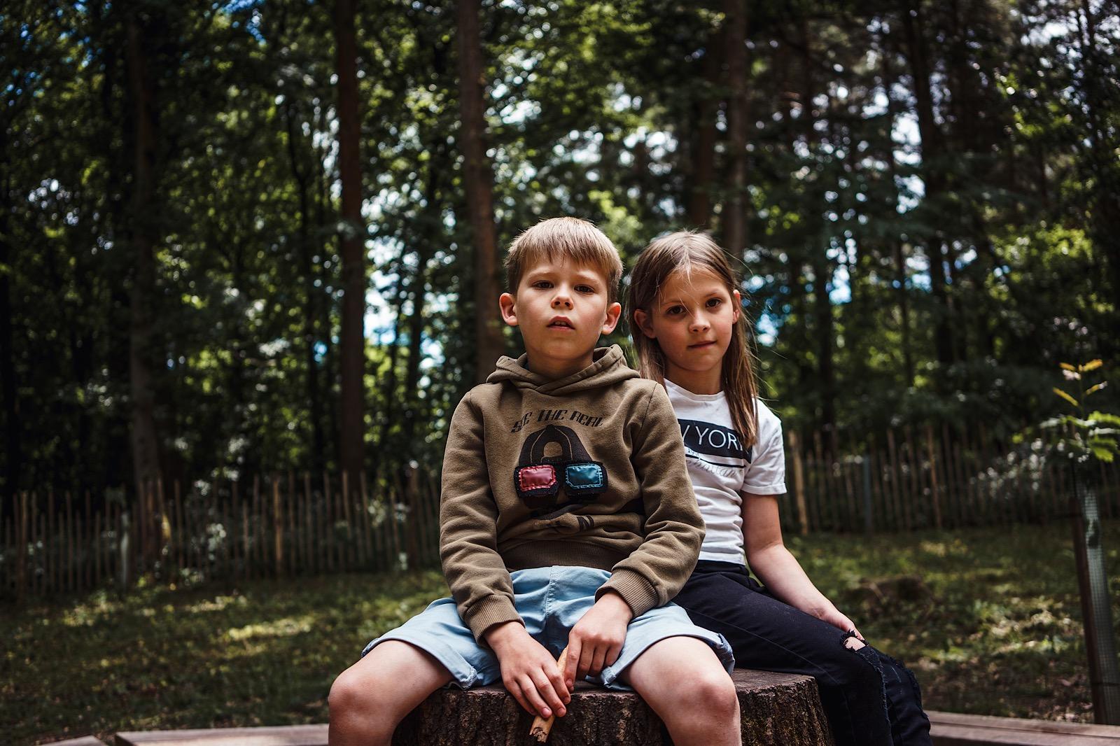boy and girl sat on tree stump