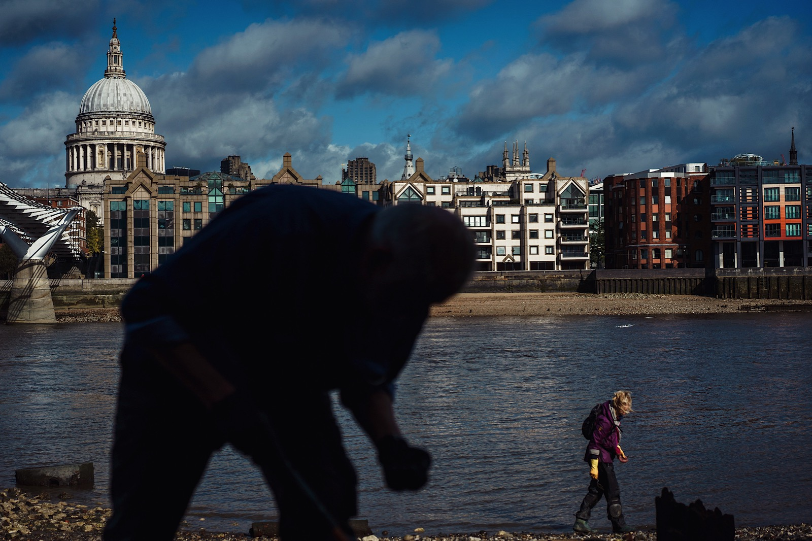 Mudlarkers searching the banks of the River Thames with St Pauls in background