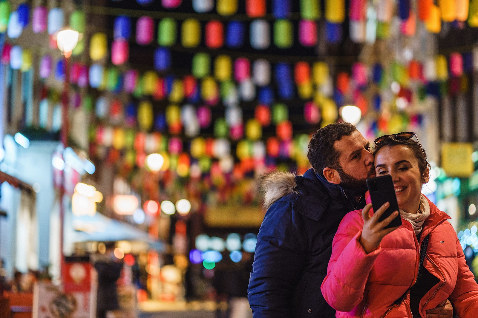Man kissing woman's head as she looks on phone with colourful lanterns