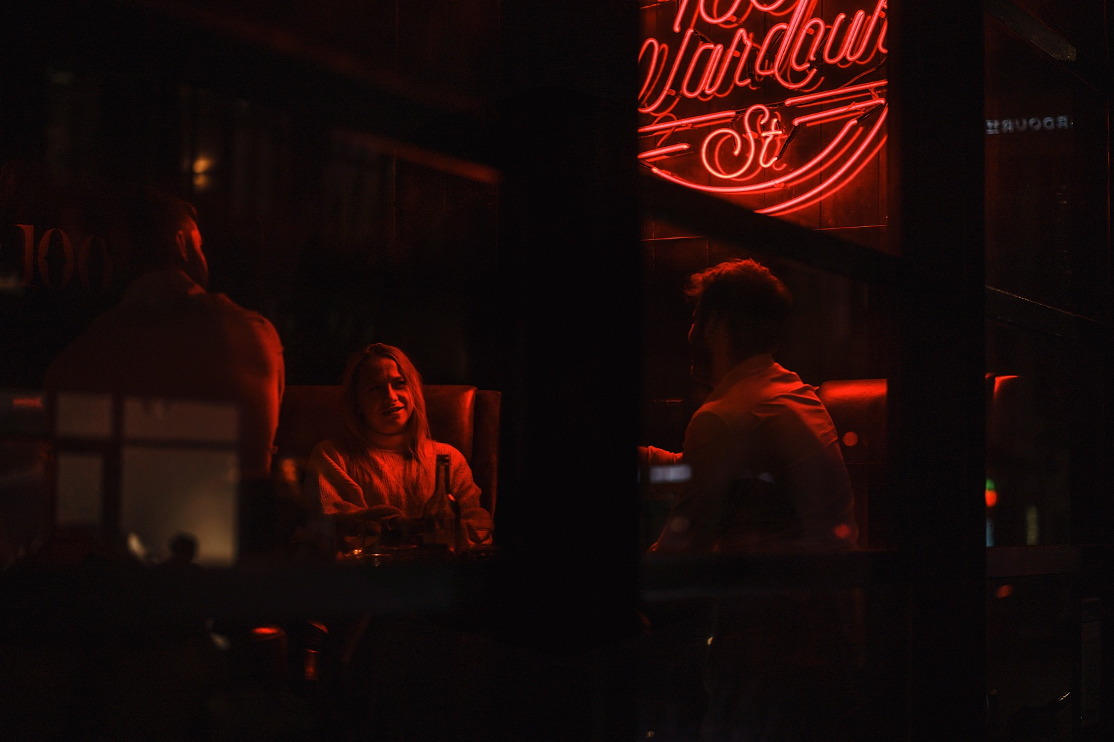 People in restruant talking under red neon sign