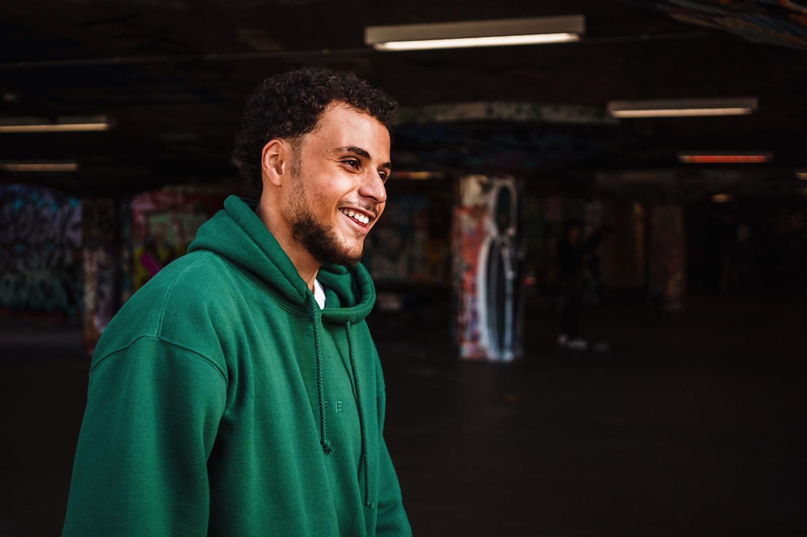 Man in green hoodie at skate park grinning