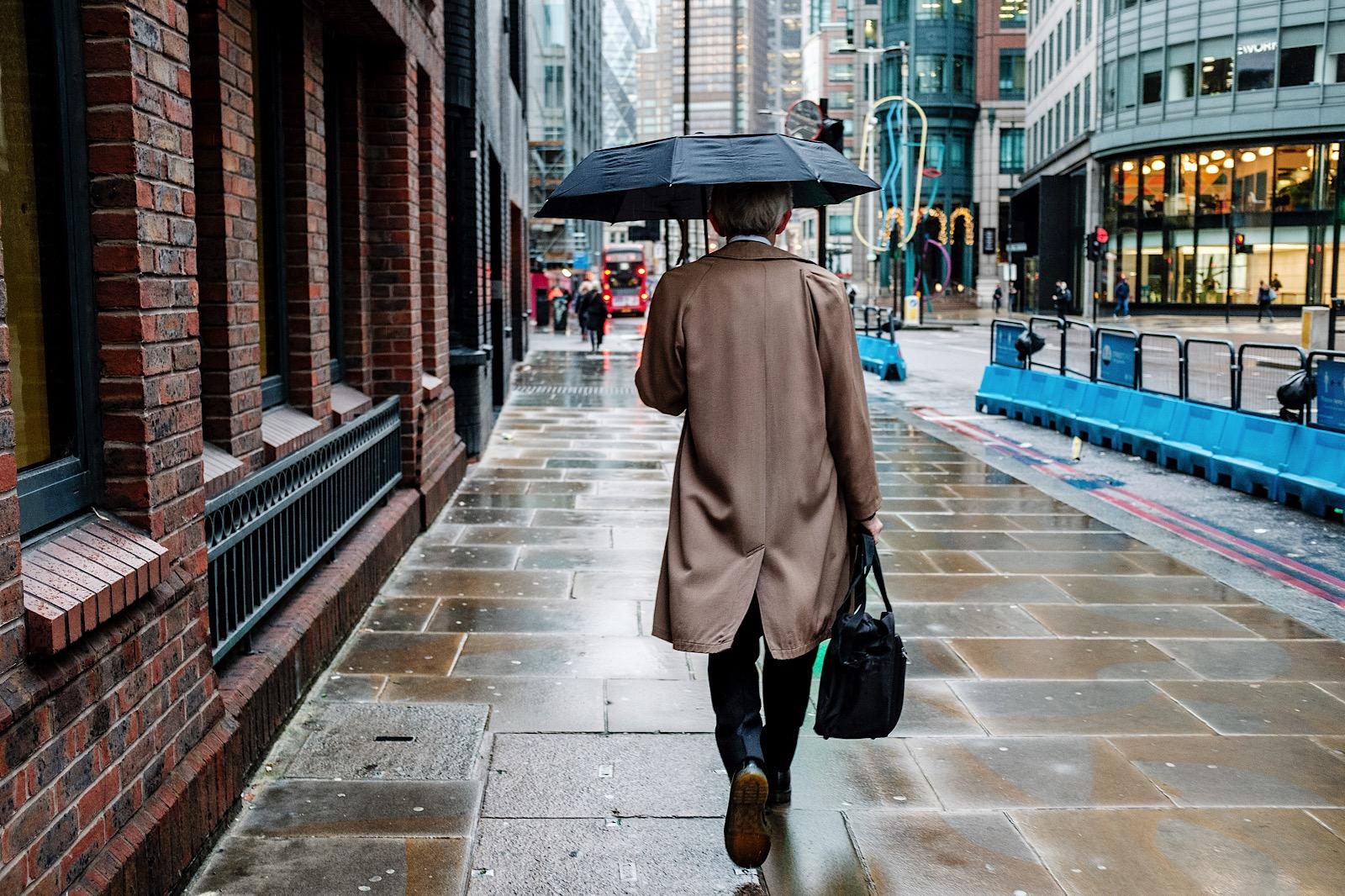 Business Man in rain mac with umbrella walking through streets of London