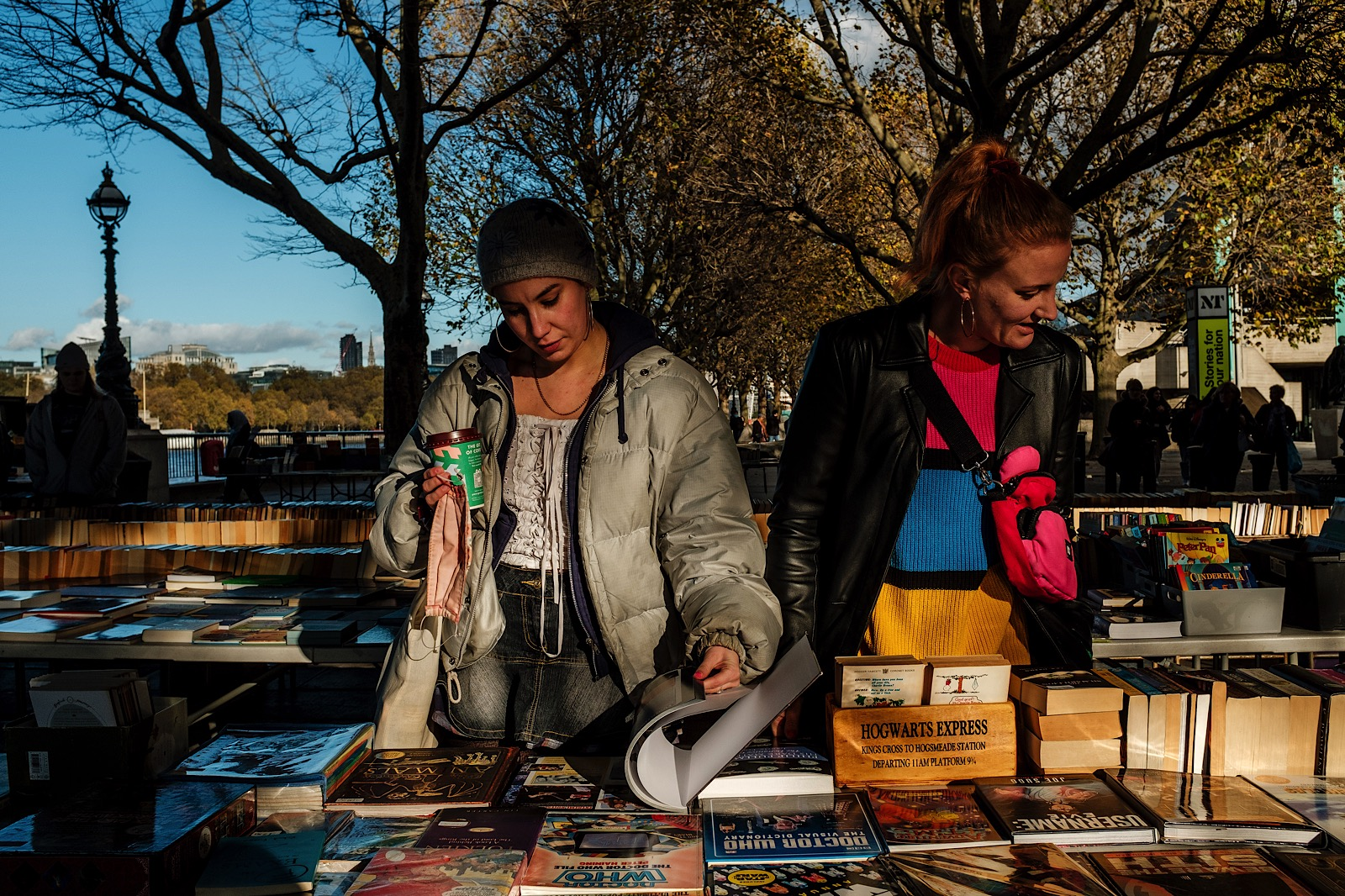 2 women browsing book stalls in market on Banks of River Thames, London