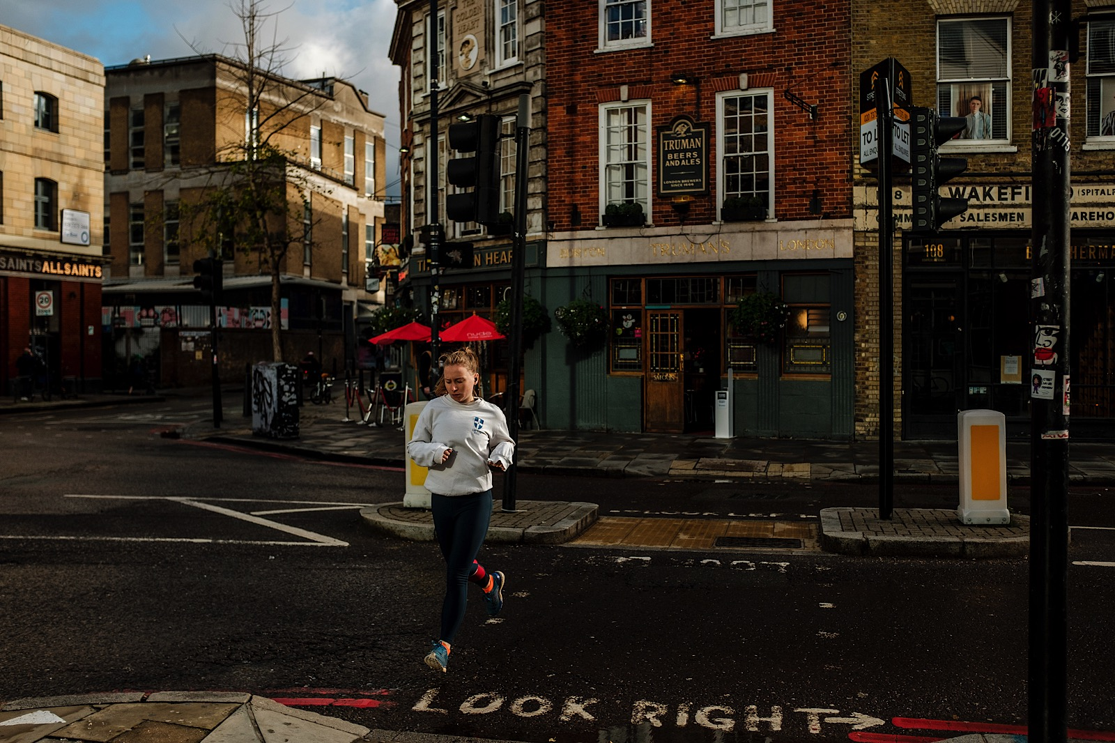 Street Photography showing female runner at pedestrian crossing in London