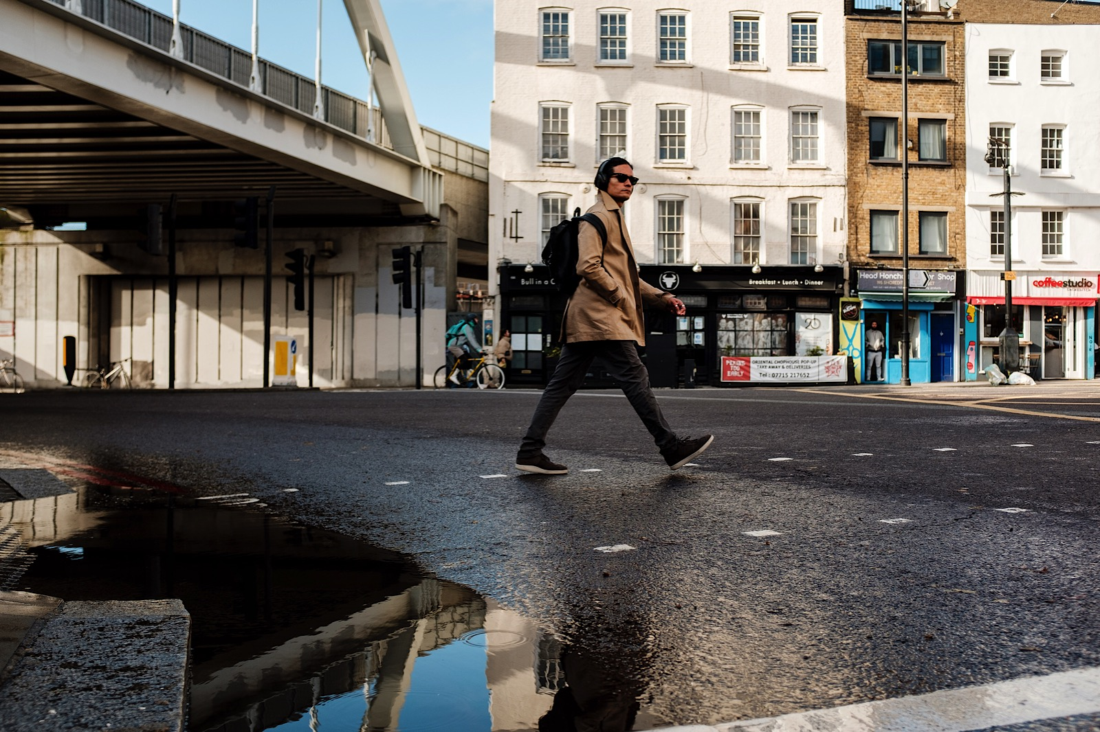 Man with headphones and sunglasses crossing road in central London