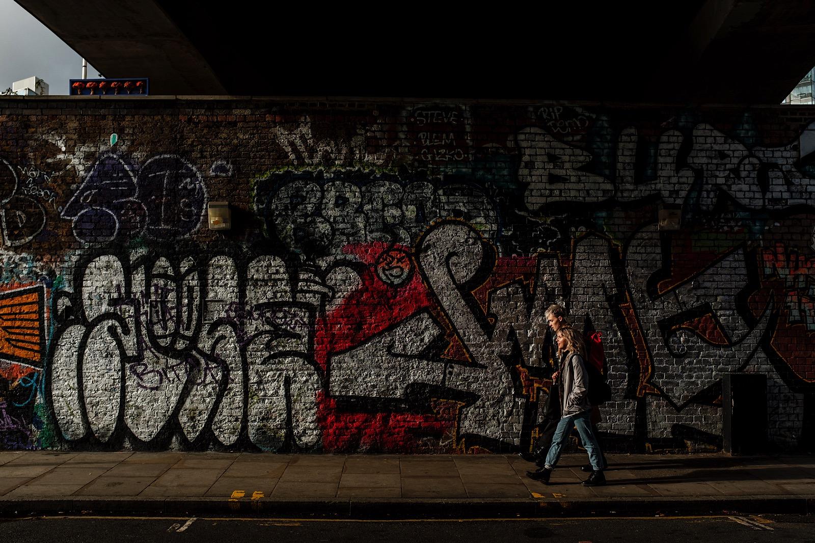 Couple walking in front of Street Art in London