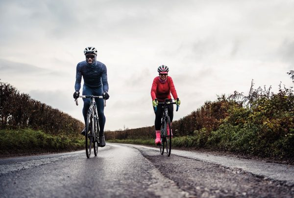Male and female cyclists on quiet country road