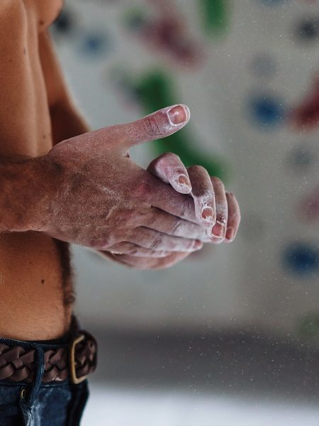 Topless Man rubbing chalk on hands in rock climbing centre