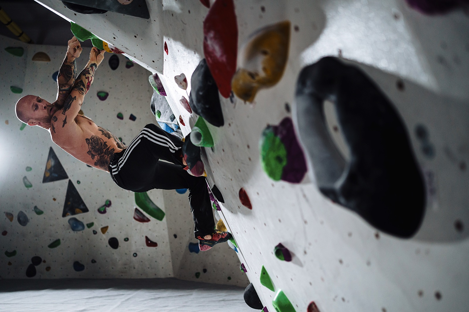 Bare chested man with tattoos on indoor climbing wall