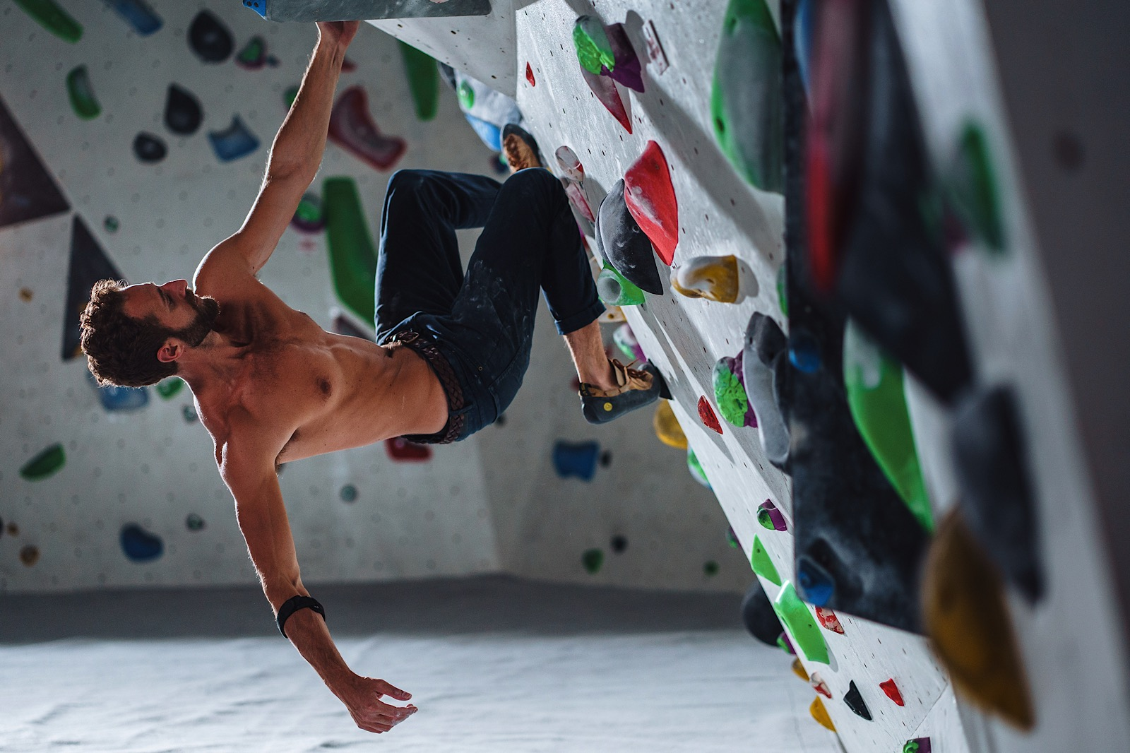 Bare chested rockclimber on wall holding on with one arm on overhang