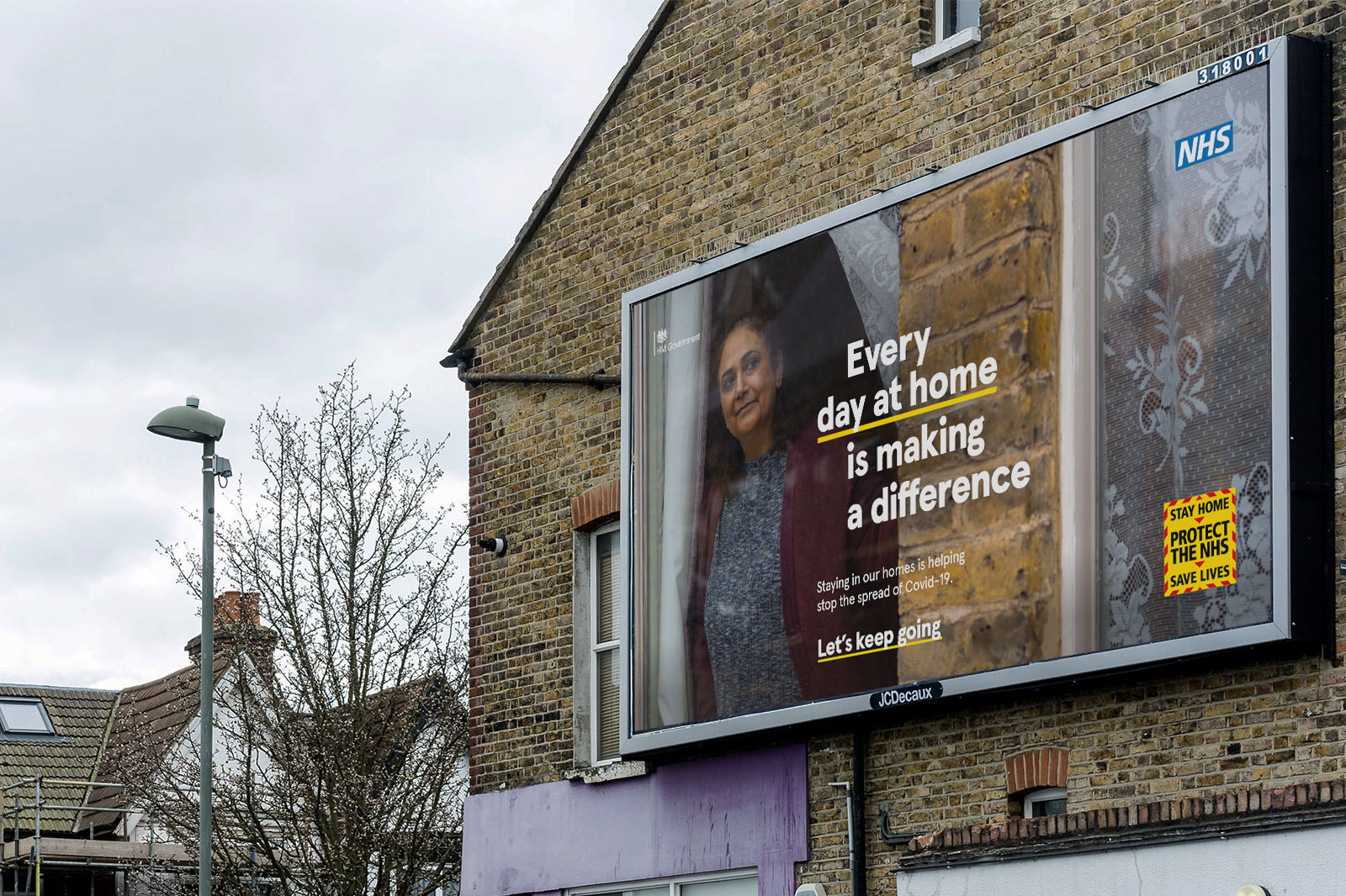 Billboard on side of house from part of the Let's Keep Going NHS and UK government Covid-19 Campaign showing women looking out of window